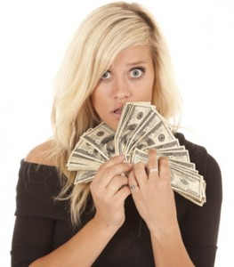 Woman looking at money with shocked expression